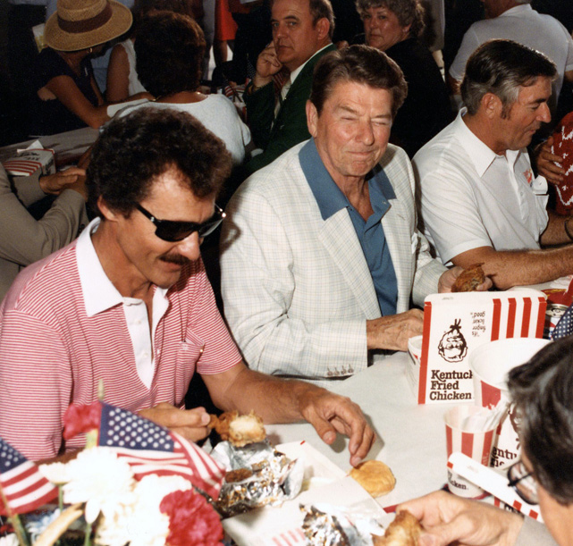DAYTONA BEACH, FL - JULY 4:  United States President Ronald Reagan enjoys a fried chicken lunch with NASCAR greats Richard Petty at a banquet hall in Daytona Beach.