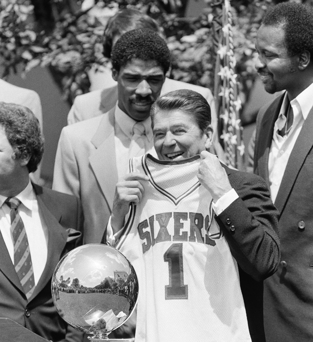 Reagan holds up a Philadelphia 76ers basketball jersey presented to him by the team after they won the 1982-83 NBA title. Behind the president are Julius Erving and Moses Malone.