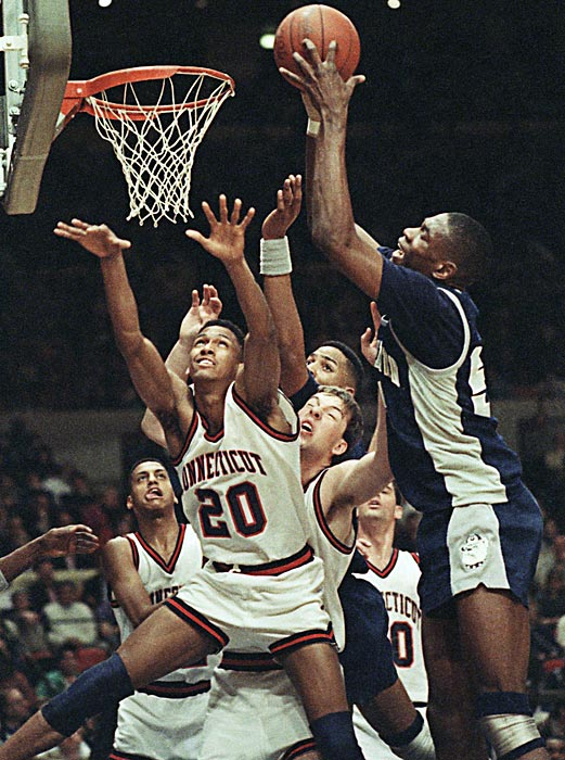 Georgetown center Dikembe Mutombo towers over Connecticut defenders during a 65-60 loss to the Huskies.