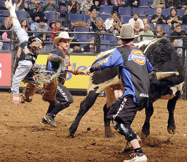 Dickies DuraBullfighters Frank Newsom (left) and Jesse Byrne (right) move in to protect Travis Briscoe of Edgewood, N.M., after he scored 82 points on Cooper Tires War Paint.