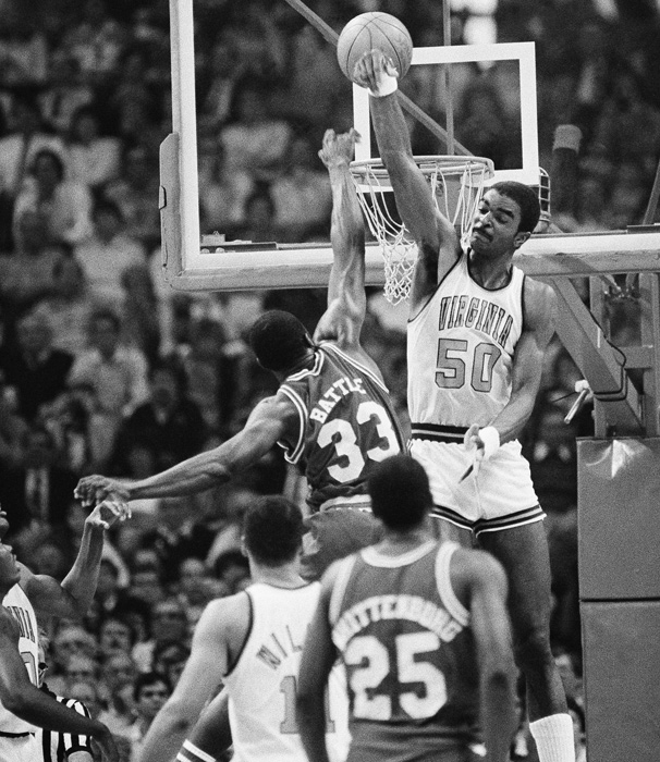 Virginia's Ralph Sampson, at 7-foot-4, fails to block this shot by N.C. State forward Alvin Battle in the 1983 championship game. The Wolfpack won 81-78.