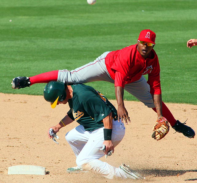 Oakland Athletics catcher Josh Donaldson (bottom) forces Los Angeles Angels shortstop Jean Segura into a split, but can't break up the double play during a spring training game in Phoenix, Ariz.