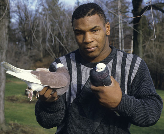 Casual portrait of Tyson holding pigeons in each hand.