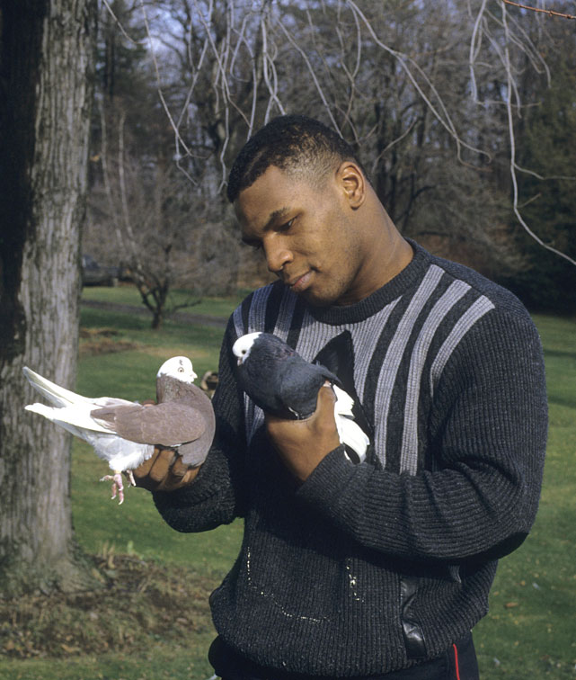 Tyson holding pigeons in each hand.