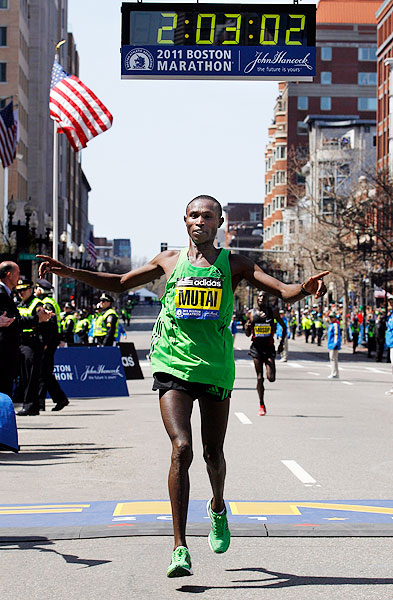 Kenya's Geoffrey Mutai crosses the finish line to set a new Boston Marathon record in the men's division of the 115th Boston Marathon.  Because the marathon had a tailwind on a downhill course, Mutai's time is not considered a world record.
