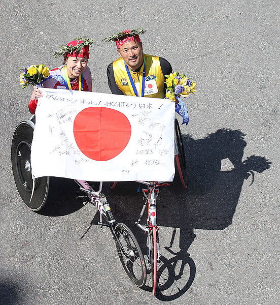 Wakako Tsuchida (left) and Masazumi Soejima, both from Japan, celebrate their victory together after winning their respective wheelchair divisions in the 115th Boston Marathon.