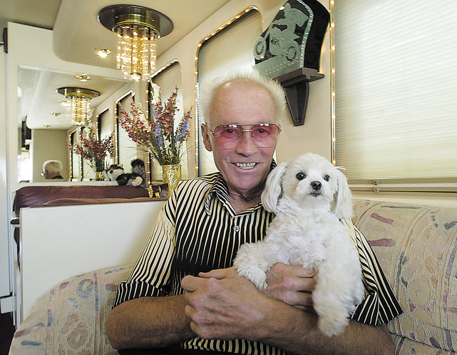 "The stuntman holds his dog, Rocket, in his home in Butte, Mont., in 2001. The town hosts ""Evel Knievel Day"" every July to celebrate the local hero."