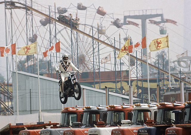 The stuntman sets a new record for motorcycle jumps by sailing over 13 Mack trucks in 1974 at the Canadian National Exhibition Stadium in Toronto.