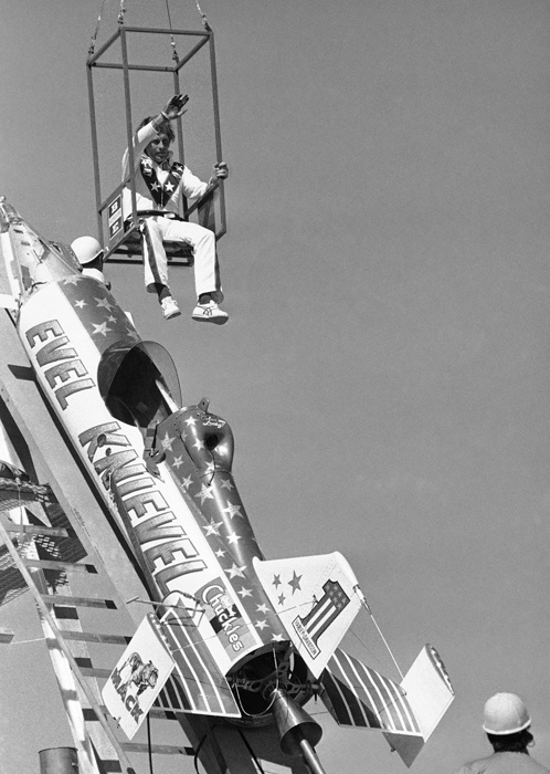 Knievel waves to the crowd as he is being lowered into his $150,000 Sky-Cycle for a test run. Unfortunately, Knievel was unable to clear the canyon in any of his test runs, but went through with the attempt anyway.