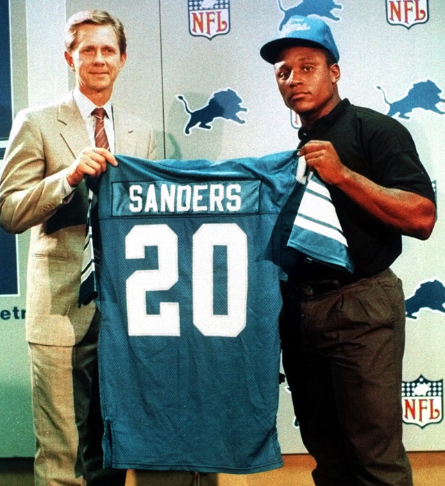 The explosive Oklahoma State running back holds his jersey with Lions vice president of finance, Chuck Schmidt. Sanders rushed for 15,269 yards in his career, but he abruptly retired in 1999 despite being a near lock to break Walter Payton's all-time rushing record the following season.