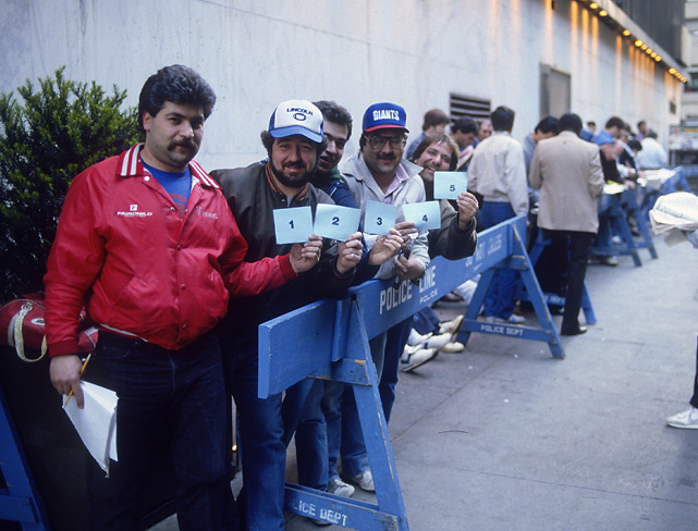 Draftniks hold up cards with their entry number as they wait for the doors to open. Tickets for the draft are free and available on a first-come, first-served basis. Since 2006, the draft has been held at Radio City Music Hall in New York.