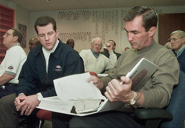 Denver Broncos head coach Mike Shanahan compares notes with Ted Sundquist, the team's director of college scouting, in the War Room during the NFL draft at Broncos headquarters in Denver. The Broncos selected wide receiver Marcus Nash with the final pick in the first round.