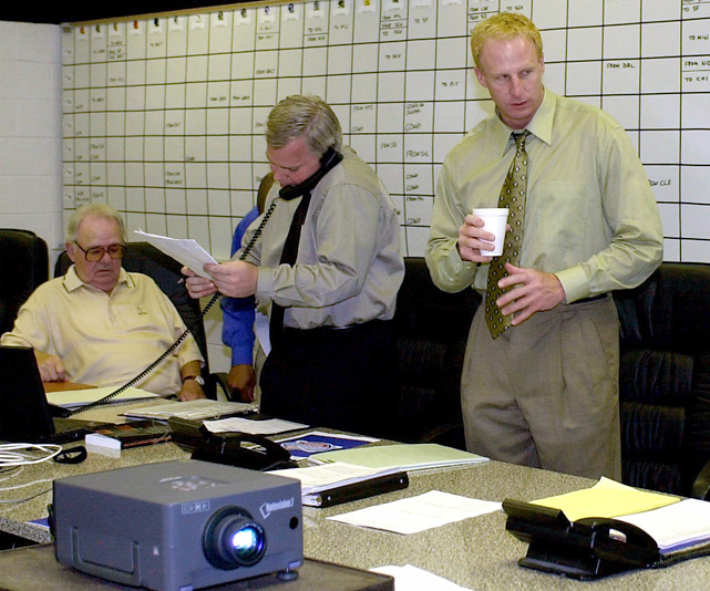 New Orleans Saints coach Jim Haslett (center) talks with assistant general manager Charles Bailey (right) as general manager Randy Mueller talks on the phone at the start of the draft. The Saints selected Darren Howard with the 33rd overall pick.