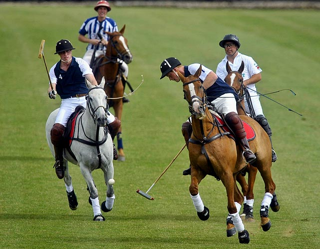 Prince Harry hits the ball forward (with his brother Prince William close behind) during the Chakravarty Cup polo match at Beaufort Polo Club, near Tetbury, Gloucestershire.