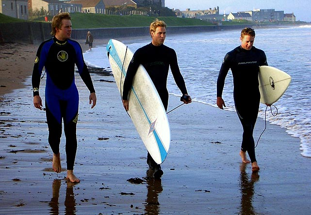 Prince William (center) carries a surfboard as he walks with two friends along the shoreline at St. Andrews in Scotland.