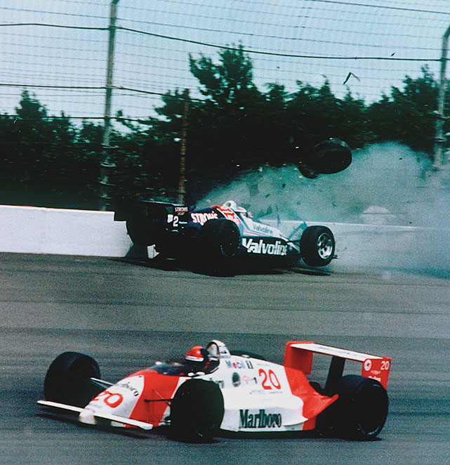 "After Tero Palmroth lost a tire to bring out the yellow flag on lap 181 of the 1989 Indy 500, racing resumed on lap 186 with Al Unser Jr. on Emerson Fittipaldi's tail. Unser took the lead four laps from the finish. Fittipaldi charged after Unser until the two encountered traffic on lap 199. As Fittipaldi pulled even with Unser heading into Turn 3, the two touched and Unser's car slammed into the outside wall. Fittipaldi kept his car under control and took the checkered flag. Unser climbed out of his wreckage, walked up the track and gave Fittipaldi a ""thumbs-up"" salute."