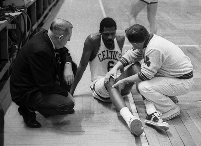 A trainer checks on the injured center during a game in 1967.