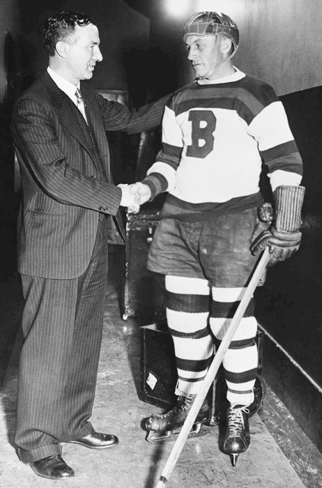 Shore, a four-time Hart Trophy-winner as the NHL's MVP, chats with coach Art Ross before his return to the ice in 1934. Shore had been suspended for 16 games after he flattened Toronto's Ace Bailey from behind, causing Bailey's head to hit the ice. The blow left Bailey with a fractured skull. Shore led Boston to the 1929 and 1939 Stanley Cups.