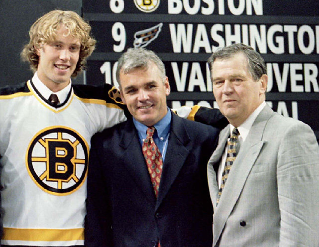 Jumbo Joe poses with assistant general manager Mike O'Connell (middle) and president/GM Harry Sinden after being selected by Boston first overall in the NHL draft. The 6-4, 230-pound center was a three-time All-Star during his eight seasons with the Bruins.