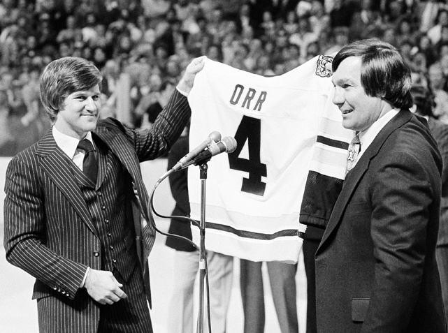 The Hall of Fame defenseman stands alongside former captain John Bucyk as Orr's No. 4 is retired during a ceremony before an exhibition game. During his 10 years with the Bruins, Orr led the NHL in points twice and in assists five times, winning the Norris Trophy as best defenseman eight consecutive years (1968-75).