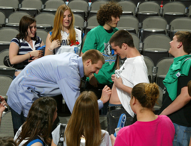 Before a game against the Bucks, Nowitzki signs autographs for fans.