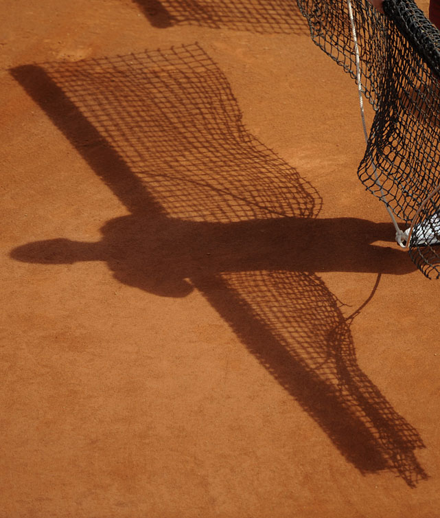 The shadow of a ball boy holding a court cleaning net is seen.