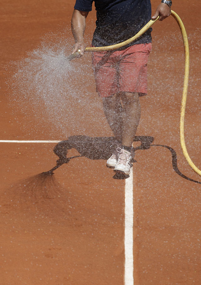 A stadium worker waters the clay court between sets as David Ferrer of Spain plays Julien Benneteau of France.