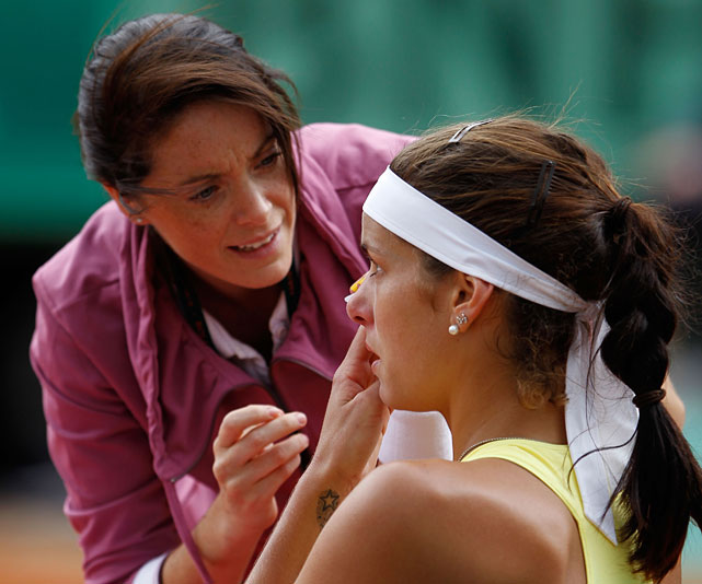 Julia Georges receives assistance after losing a contact lens during Friday's match.