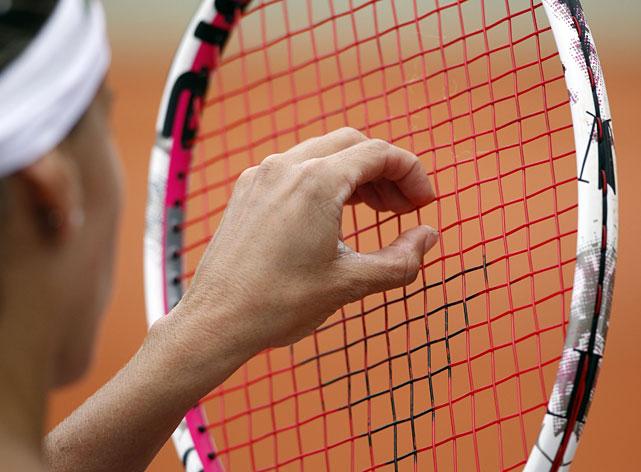 Gisela Dulko checks her racket strings during her third-round match with Sam Stosur.