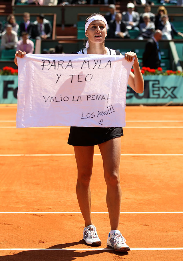 Gisela Dulko holds up a message as she celebrates her victory. She will face Marion Bartoli in the Round of 16.