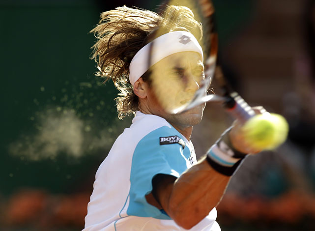 Spain's David Ferrer returns the ball to France's Gael Monfils during their fourth-round match, which was suspended in the fourth set for darkness.