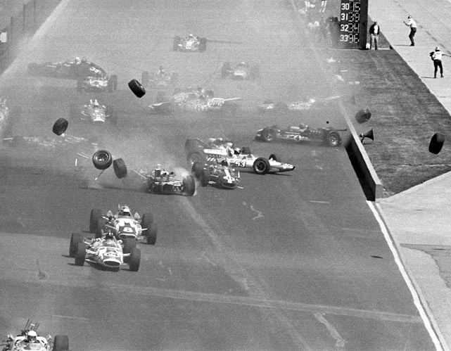 Tires fly off as cars collide in a pileup near the start of the Indy 500. More than half of the 33 cars in the field were damaged and forced out of the race. All drivers escaped serious injury.