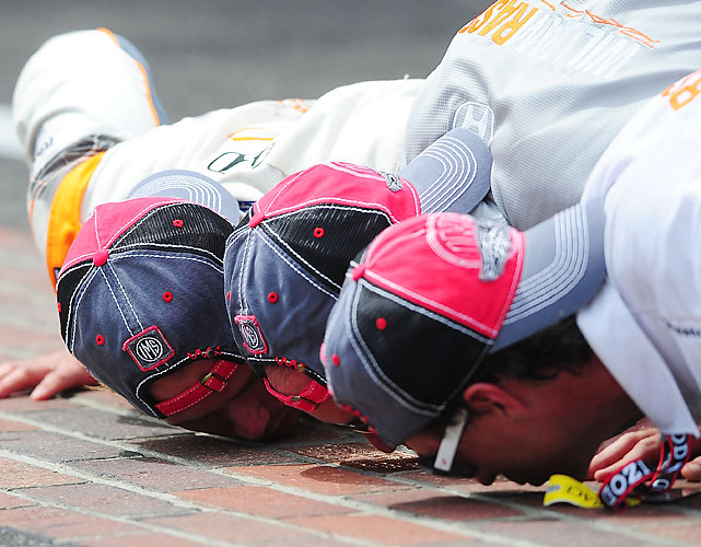 Dan Wheldon kisses the bricks with his team owner Bryan Herta and a crew member after winning the 95th running of the Indianapolis 500.