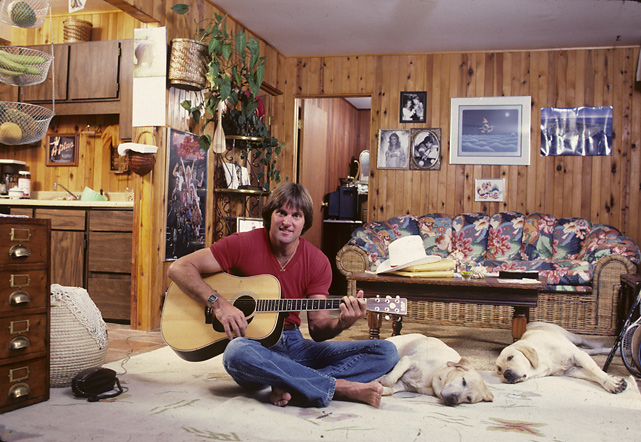 In this SI photo shoot, Jenner shows off his guitar skills as his two dogs relax beside him.