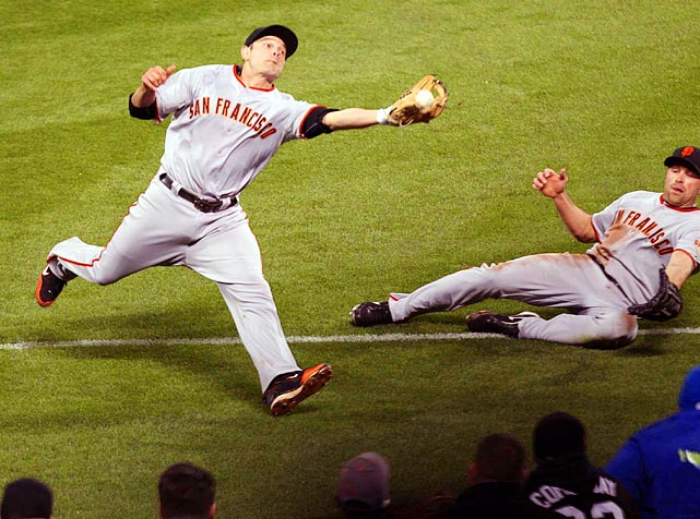 Luckily for Giants outfielder Nate Schierholtz (right), whose slide came up short, second baseman Freddy Sanchez was in position to nab a foul ball during the Giants' 2-0 victory over the Mets on May 4.