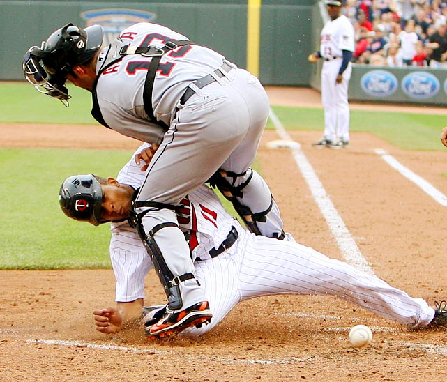 Minnesota Twins outfielder Ben Revere (bottom) beats the tag from Detroit Tigers catcher Alex Avila (top), but it looked painful. The Tigers went on to win 9-7.