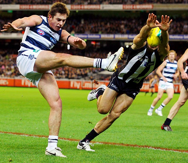 Well, that's one way to play defense. Chris Tarrant (right) of the Collingwood Magpies blocks a shot from the Geelong Cats' Daniel Menzel (left) during an AFL match on May 13.