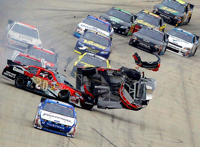 Clint Bowyer (center) spins in the air after colliding with Joey Logano (left) during a NASCAR Nationwide Series race at Dover International Speedway. Carl Edwards avoided the wreck for his third Nationwide win of 2011.