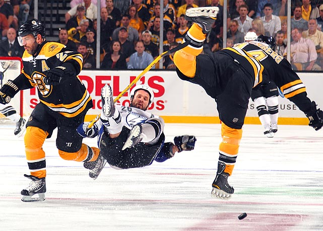 Tampa Bay Lightning rightwinger Martin St. Louis (center) is knocked off his skates by Boston Bruins rightwinger Mark Recchi (left) and defenseman Dennis Seidenberg during the Bruins' 1-0 victory in Game 7 of the Eastern Conference finals.