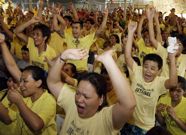 Filipino detainees celebrate as they watch Pacquiao knock down Mosley in the third round of their fight during a live television broadcast inside the Makati city jail.