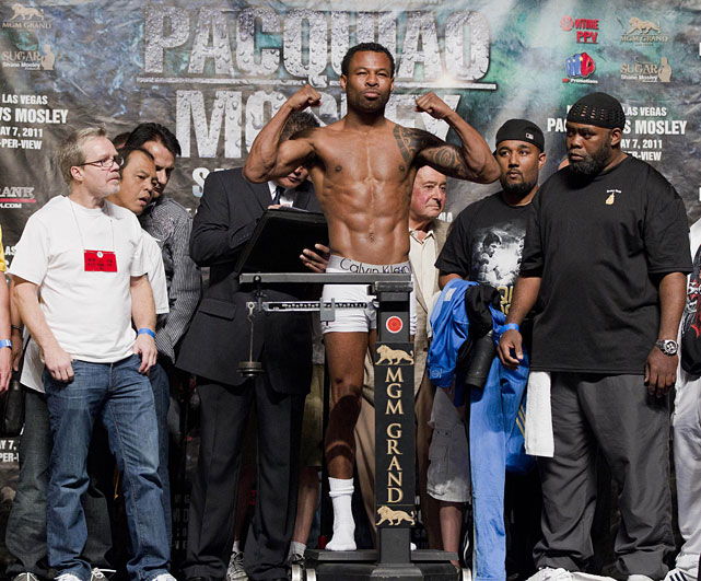 Mosley (center) stands on the scale during the weigh-in while flanked by his trainer Naazim Richardson (left) and Pacquiao's trainer Freddie Roach (right).