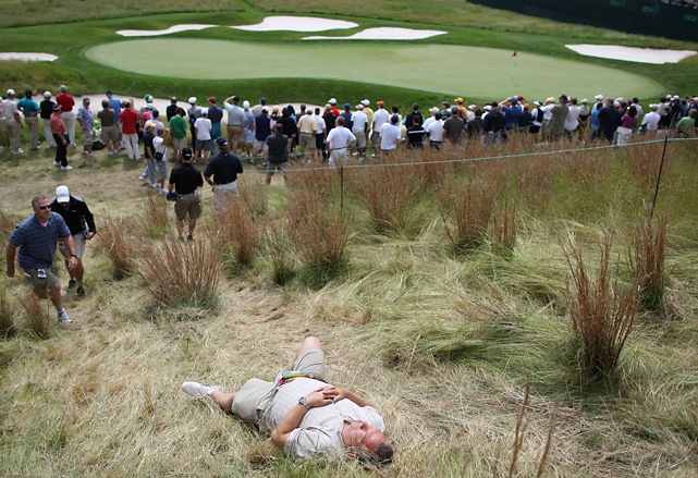 As fans clamor to get a good view of the 16th green at Bethpage, a fan escapes to a less populated area for a quick nap.