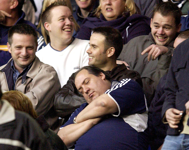 This sleeping fan provides amusement for those surrounding him during the first half of a Tottenham-Middlesbrough match.