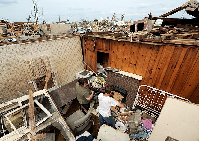Two residents try to salvage belongings in a Tuscaloosa home on May 1.