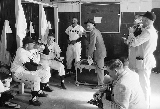 Mays and his teammates chat with reporters before the Giants' inaugural game in San Francisco in 1958.