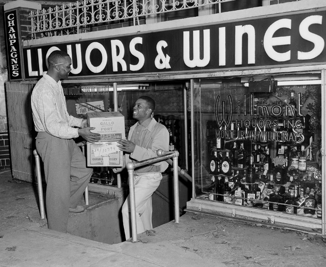 Giants outfielder Monte Irvin hands liquor boxes to Mays in front of their Willmont Liquors, Inc. store in Brooklyn.