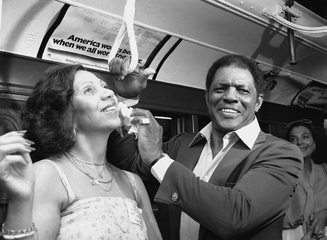 "Mays wipes sweat from his wife's face as they ride the ""A"" train to the former sight of the Polo Grounds, the long-time home of the New York Giants. The Colgate women's games paid tribute to Mays on Aug. 2, 1979, the day this photo was taken. He was inducted into the Hall of Fame three days later."