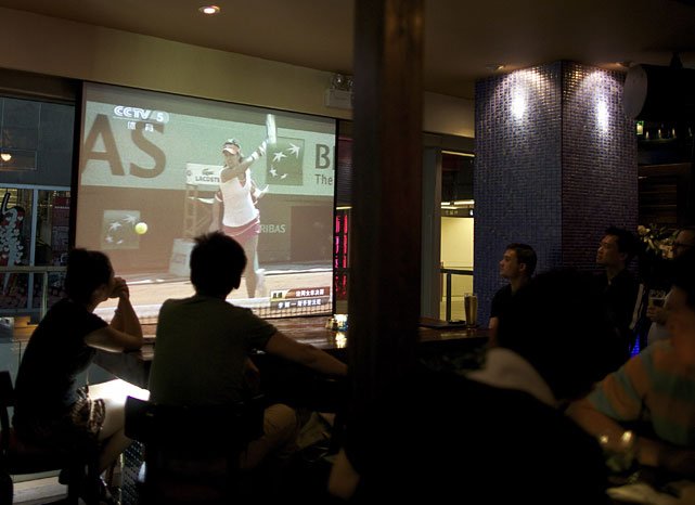 Chinese people watch a live telecast of the Li Na-Francesca Schiavone match at a pub in Beijing.