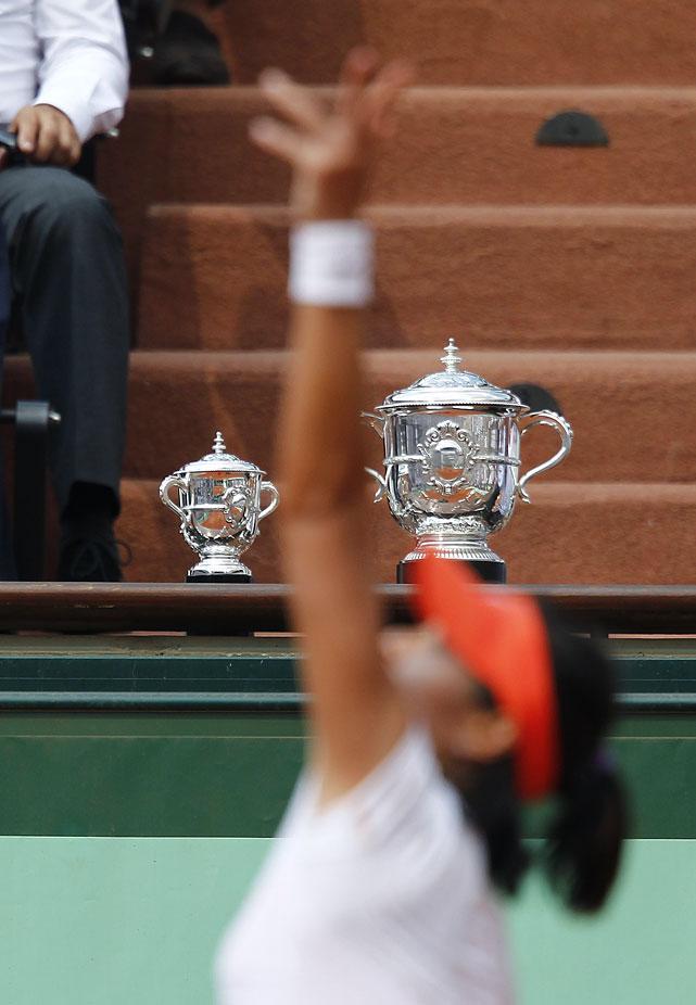 Li Na serves near the French Open trophies.