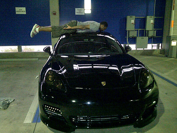 Agent Zero, clearly unimpressed by Howard's Rolls-Royce planking, poses for his photo op on Howard's precious Porsche.